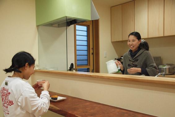 対面キッチンは家族の会話も弾みます。 レンジフードのペパーミントグリーンはT様のお好きな色を塗装させていただきました。 置くの収納棚もオリジナルで製作。 システムキッチンの棚よりもローコストでつくることができます。