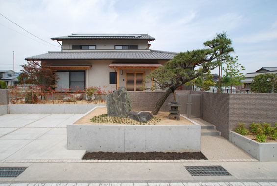 ※写真:外観とアプローチ。駐車場も2台ゆったり停めれるように。印象的な松の木は、ご両親がお住まいされていた時からのものを引継いで。この他にも5本の植栽を大切に植え替えさせていただきました。