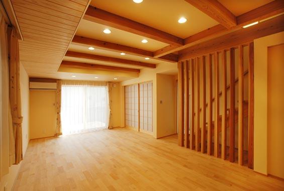 ※写真:台所から階段のあるリビングを眺める。メープルの無垢の床材、壁は珪藻土、そして柱は桧、梁は杉の無垢材で。